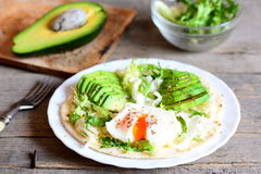 Healthy breakfast recipe. Homemade flour tortilla with a poached egg, avocado slices, napa cabbage, salad mix, sauce and spices Royalty Free Stock Photography