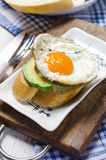 Healthy breakfast. Sandwich with rye bread, avocado and fried eggs Stock Image