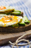 Healthy breakfast. Sandwich with rye bread, avocado and fried eggs Royalty Free Stock Photos