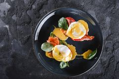 Healthy breakfast sandwiches. Bread toasts with Poached eggs or eggs Benedict, fresh vegetables, avocado, fillet salmon. Bacon on dark background. Clean eating stock photo