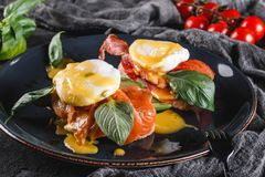 Healthy breakfast sandwiches. Bread toasts with Poached eggs or eggs Benedict, fresh vegetables, avocado, fillet salmon. Bacon on dark background. Clean eating stock photos
