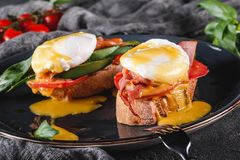 Healthy breakfast sandwiches. Bread toasts with Poached eggs or eggs Benedict, fresh vegetables, avocado, fillet salmon. Bacon on dark background. Clean eating royalty free stock images