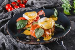Healthy breakfast sandwiches. Bread toasts with Poached eggs or eggs Benedict, fresh vegetables, avocado, fillet salmon. Bacon on dark background. Clean eating stock photography