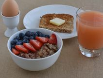 Healthy Breakfast Scene with grapefruite juice, boiled egg, sprouted grain toast, and steel cut oatmeal with fruit. Royalty Free Stock Photography