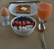Healthy Breakfast Scene with grapefruite juice, boiled egg, sprouted grain toast, and steel cut oatmeal with fruit Stock Image