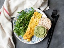 Healthy breakfast - scrambled eggs, arugula and bread with pesto on gray background. Perfect eggs omelette with fresh arugula and stock photo