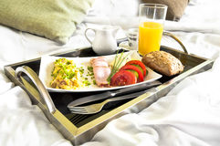 Healthy breakfast served to bed. Scrambled eggs with tomatoes, cucumber and orange juice Stock Images