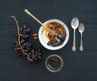 Healthy breakfast set. Bowl of oat granola with yogurt, fresh grapes, almond and  honey over black wooden backdrop Royalty Free Stock Image