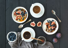 Healthy breakfast set. Bowls of oat granola with yogurt, fresh blueberries and figs, coffee, honey, over black wooden Stock Photo