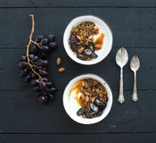 Healthy breakfast set. Bowls of oat granola with yogurt, fresh grapes, almond and  honey over black wooden backdrop Royalty Free Stock Image