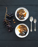 Healthy breakfast set. Bowls of oat granola with yogurt, fresh grapes, almond and  honey over black wooden backdrop Stock Image