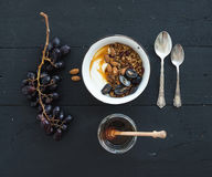 Healthy breakfast set. Bowls of oat granola with yogurt, fresh grapes, almond and  honey over black wooden backdrop Royalty Free Stock Photography