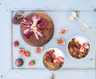 Healthy breakfast set. Bowls of oat granola with yogurt, fresh strawberries, figs, pomegranate andd  honey over light Royalty Free Stock Image