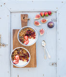 Healthy breakfast set. Bowls of oat granola with yogurt, fresh strawberries, figs, pomegranate  Royalty Free Stock Photography