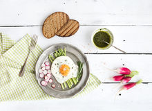 Healthy breakfast set. Fried egg with asparagus, radishes, green sauce and bread on vintage metal plate over white Royalty Free Stock Photography