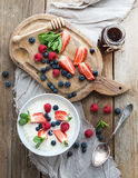 Healthy breakfast set. Rice cereal or porridge with berries and honey over rustic wood backdrop Stock Photography