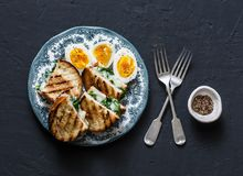 Healthy breakfast or snack - boiled farm eggs, spinach, grilled cheese sandwiches on dark background. Top view royalty free stock photography