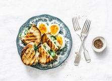 Healthy breakfast or snack - boiled farm eggs, spinach, grilled cheese sandwiches on light background Royalty Free Stock Photo
