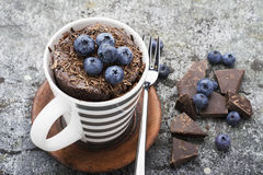 Healthy breakfast or snack. Chocolate mug cupcake with blueberries and chocolate chips in a gray striped ceramic mug on Royalty Free Stock Image