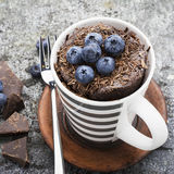 Healthy breakfast or snack. Chocolate mug cupcake with blueberries and chocolate chips in a gray striped ceramic mug on Royalty Free Stock Photo