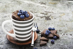Healthy breakfast or snack. Chocolate mug cupcake with blueberries and chocolate chips in a gray striped ceramic mug on Stock Image