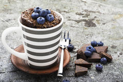 Healthy breakfast or snack. Chocolate mug cupcake with blueberries and chocolate chips in a gray striped ceramic mug on Stock Photo