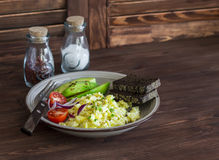 Healthy breakfast or snack - eggs scramble, avocado and cherry tomatoes. On a brown wooden surface Stock Images