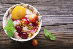 Healthy breakfast snack. Marble Portion bowl full of cherry smoothie with natural yogurt, ripe berries, fruits, bee Royalty Free Stock Image