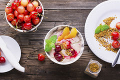 Healthy breakfast snack. Marble Portion bowl full of cherry smoothie with natural yogurt, ripe berries, fruits, bee Royalty Free Stock Photography