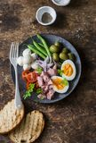Healthy breakfast or snack - plate of canned tuna, green beans, mozzarella cheese, tomatoes, boiled egg, olives, grilled bread a w Stock Photo