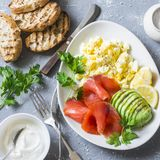 Healthy breakfast or snack - smoked salmon, scramble egg  and avocado. On a gray background, top view. Healthy food. Concept Stock Photography