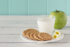 Healthy breakfast. Some cereals cookies, a milk glass and a apple on a white wooden table with a robin egg blue background. Vintage royalty free stock photography