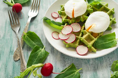 Healthy breakfast: spinach waffles with radish slices and poached eggs. On green wooden table. Selective focus Stock Image
