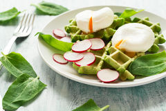 Healthy breakfast: spinach waffles with radish slices and poached eggs. On green wooden table. Selective focus Royalty Free Stock Images