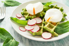 Healthy breakfast: spinach waffles with radish slices and poached eggs. On green wooden table. Selective focus Royalty Free Stock Photo