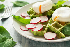 Healthy breakfast: spinach waffles with radish slices and poached eggs. On green wooden table. Selective focus Stock Photo