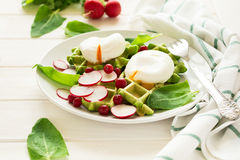 Healthy breakfast: spinach waffles with radish slices and poached eggs. On white wooden table. Selective focus Stock Photography