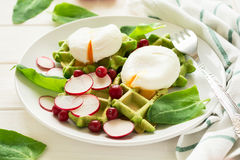 Healthy breakfast: spinach waffles with radish slices and poached eggs. On white wooden table. Selective focus Stock Image