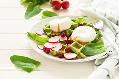 Healthy breakfast: spinach waffles with radish slices and poached eggs. On white wooden table. Selective focus Stock Photos