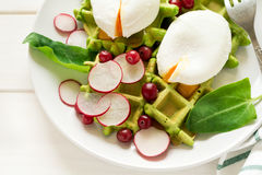 Healthy breakfast: spinach waffles with radish slices and poached eggs. On white wooden table. Selective focus Royalty Free Stock Image
