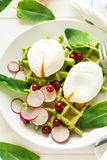 Healthy breakfast: spinach waffles with radish slices and poached eggs. On white wooden table. Selective focus Royalty Free Stock Photos