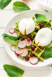 Healthy breakfast: spinach waffles with radish slices and poached eggs. On white wooden table. Selective focus Stock Images