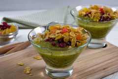 Healthy breakfast, summer dessert with smoothie kiwi, corn flakes and dried fruits Royalty Free Stock Images