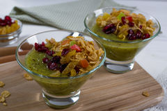 Healthy breakfast, summer dessert with smoothie kiwi, corn flakes and dried fruits in a glassware Stock Photography