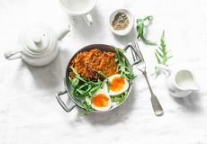 Healthy breakfast - sweet potato fritters, boiled egg, arugula salad on light background. Top view stock image