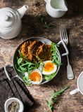 Healthy breakfast - sweet potato fritters, boiled egg, arugula salad on wooden background. Top view royalty free stock photo