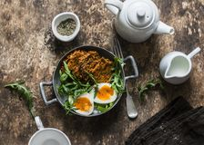 Healthy breakfast - sweet potato fritters, boiled egg, arugula salad on wooden background. Top view royalty free stock photography