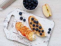 Healthy breakfast with sweet sandwiches - ricotta, blueberries, apple slices, peanut butter on white rustic wood table. Top view royalty free stock image