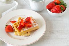 Colorful breakfast with waffles and strawberries. Healthy breakfast table with belgian waffles, exotic fruits and coffee Royalty Free Stock Images
