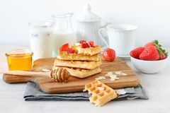 Colorful breakfast with waffles and strawberries. Healthy breakfast table with belgian waffles, exotic fruits and coffee Stock Photo